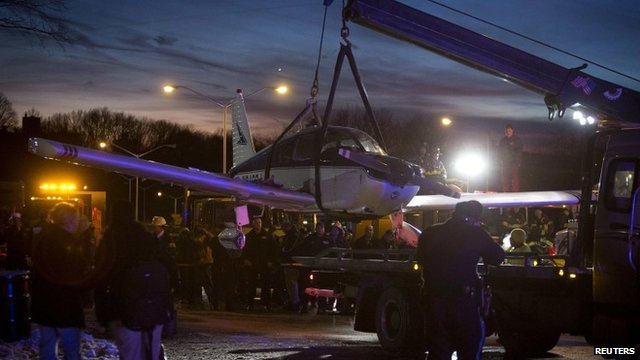 Plane being lifted onto flat bed truck