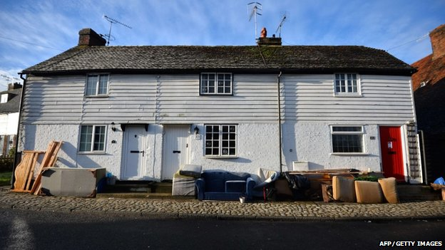 Flood damaged furniture is piled outside homes in the village of Yalding in Kent, southern England
