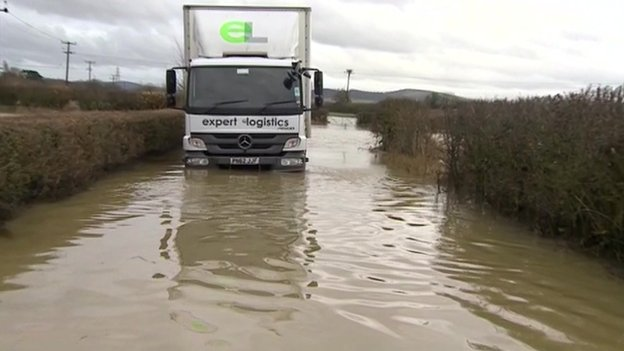 Firefighters used an amphibious vehicle to rescue two men when their lorry broke down in flood water in Tewkesbury, Gloucestershire