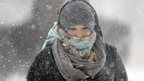 A woman walks across a street in St. Louis as snow and wind swirls around on 5 January 2014