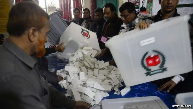 Bangladeshi election officials open a ballot box to count votes