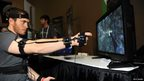 A member of the PrioVR team plays a video game wearing a full body harness with 17 body and head sensors. Each sensor contains a magnetometer, gyroscope and accelerometer to translate body motions into actions by gaming characters.
