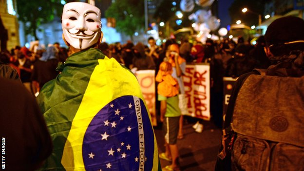 A demonstrator with a Guy Fawkes mask is pictured as clashes with the riot police erupt after a march by Brazilian workers in Rio de Janeiro on July 11, 2013 in a day of industrial action.