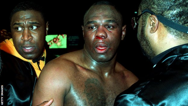 19 MAR 1994: MICHAEL BENTT OF THE USA IS LED AWAY BY HIS CORNERMEN, BADLY SHAKEN AND WITH HIS FACE BLOODIED, AFTER LOSING HIS WBO HEAVYWEIGHT TITLE FIGHT TO HERBIE HIDE OF GREAT BRITAIN.