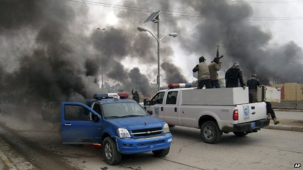 Al-Qaeda fighters patrol in a commandeered police truck in Falluja