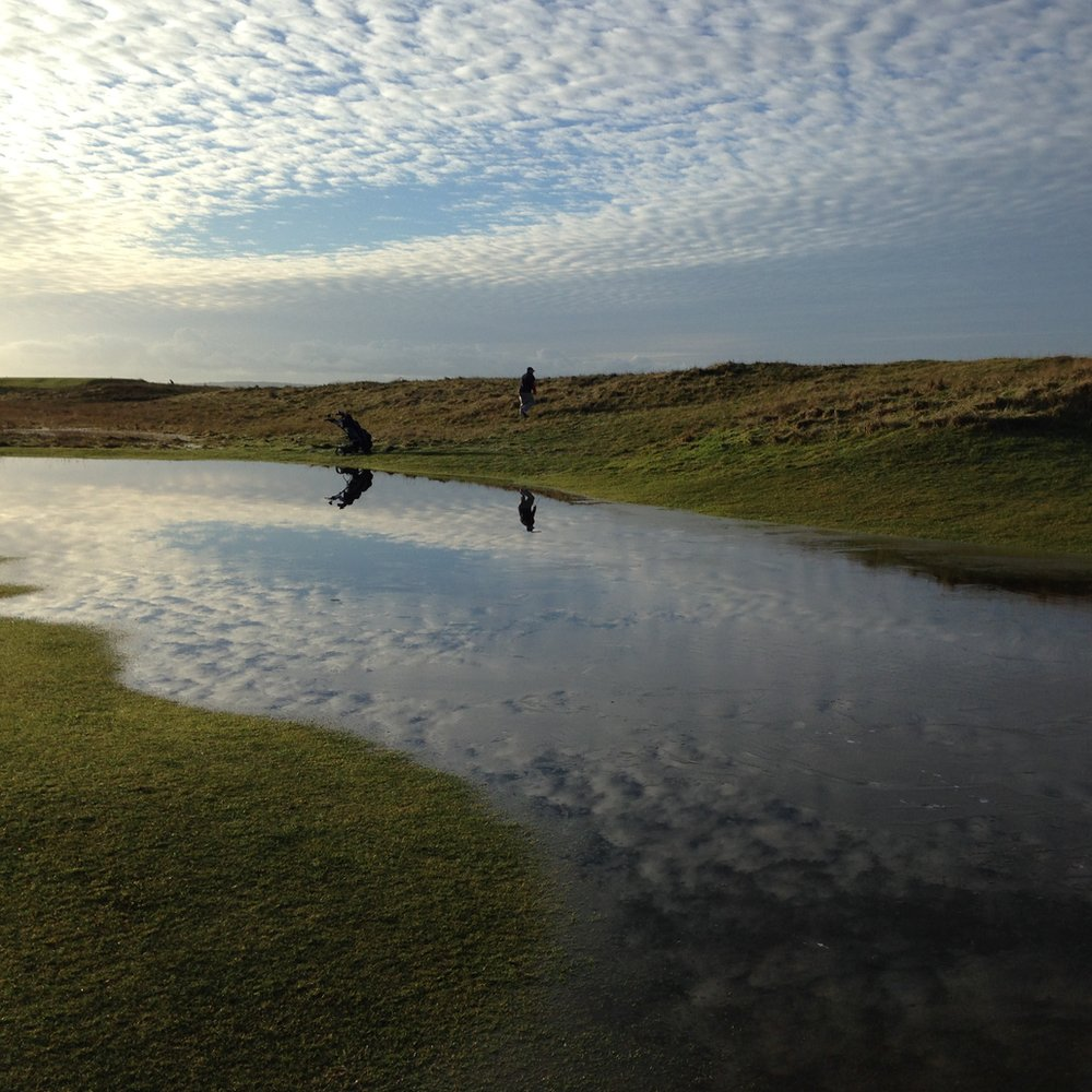 A man playing golf by a pool of water.