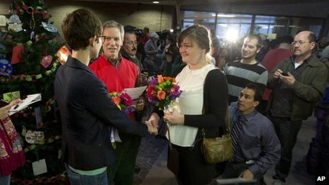 Natalie Dicou, left, and Nicole Christensen, right, are married by Salt Lake City Mayor Ralph Becker, middle, in the lobby of the Salt Lake County Clerk's Office in Salt Lake City 20 December 2013