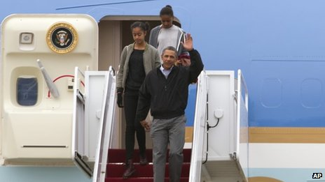 President Barack Obama accompanied by his daughters Malia and Sasha waves from Air Force One upon arrival at Andrews Air Force Base on 5 January 2014