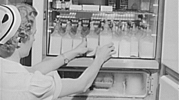 A nurse arranges formula bottles in 1942