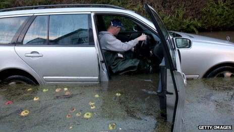 A man sits in a car with the door open - flood water is up to the driver's seat