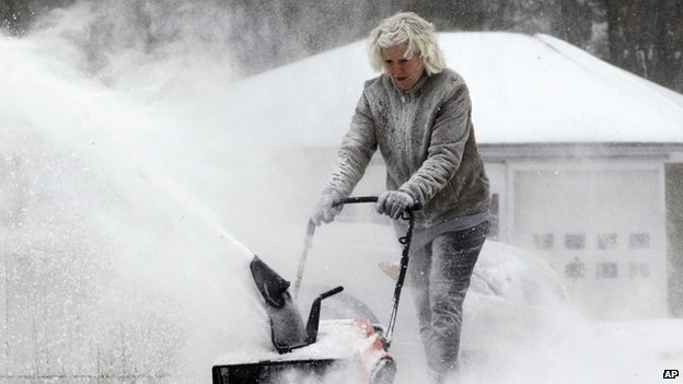 A woman snow blows her driveway in Springville, New York on 6 January 2014