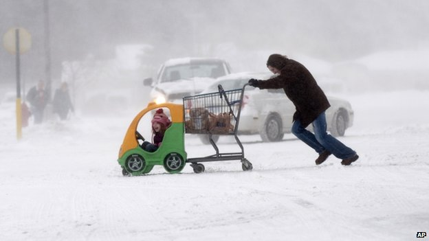 A woman pushes her daughter and their groceries through blowing snow in Saginaw Township, Michigan, on 6 January 2014