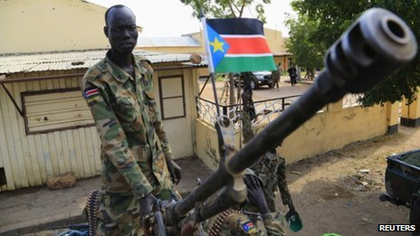 A South Sudan army soldier stands next to a machine gun mounted on a truck in Malakal town on 30 December 2013