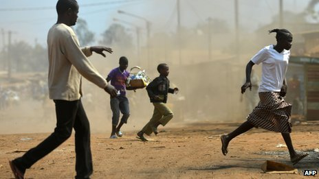Civilians run to a safe place after a grenade was thrown at the Kokoro market in the Km 5 district of Bangui on 5 January 2014