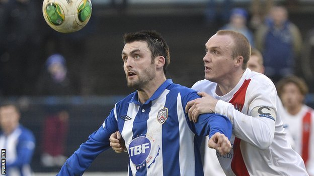 Coleraine striker Eoin Bradley shields the ball from Ards opponent Andy Hunter