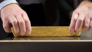An employee of the German Federal Bank puts a bar of gold on a scale during a press conference at the German Federal Bank in Frankfurt