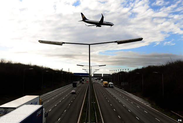 A plane coming in to land at East Midlands Airport over the M1