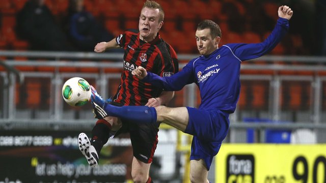 Crusaders striker Jordan Owens is beaten to the ball by Dungannon's Dermot McCaffrey
