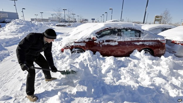 A salesmen at a car dealer digs out cars covered in snow in Indianapolis, Indiana, on 7 January 2014