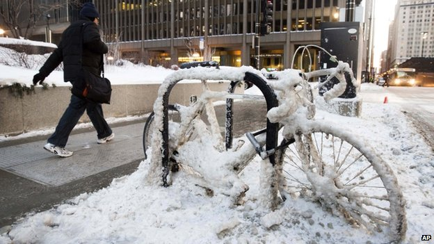 A man walks past a snow encrusted bicycle in Chicago on 7 January 2014