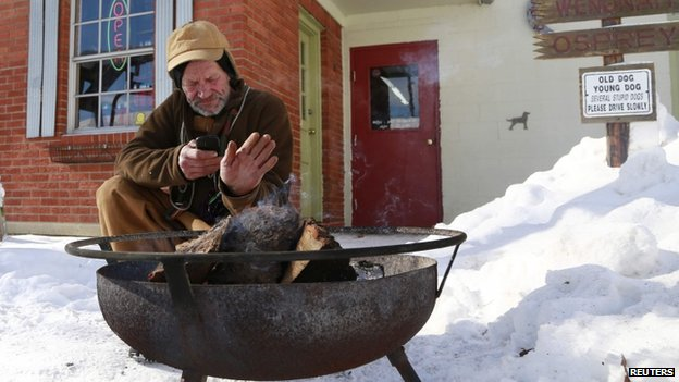 A man warms himself near a fire in Indianapolis, Indiana, on 7 January 2014