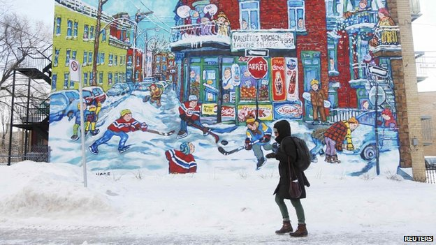 A pedestrian walks past a mural depicting a winter scene in Montreal, Quebec, on 7 January 2014