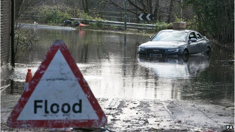 An abandoned Audi car sits in flood water in Chertsey, Surrey
