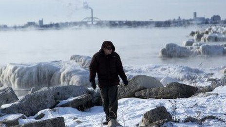 A man walks along the frozen shore of Lake Michigan in Milwaukee, Wisconsin.