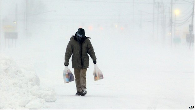 A man walks down a snow covered street in Hamburg, New York on 7 January 2014