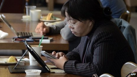 A woman using her phone and tablet PC in China