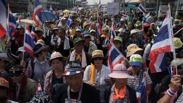 Thai anti-government protesters wave national flags during a rally in Bangkok on 7 January 2014