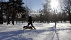A woman jogs through the snow with her dog in Missouri