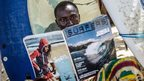 Alpha reads a surfing magazine on Bureh Beach
