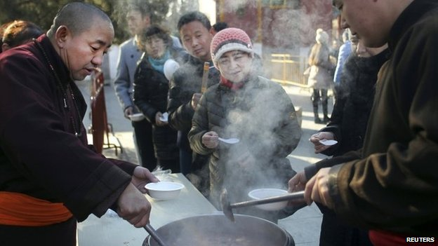 People queue up as monks pour free laba porridge at the Yonghegong Lama Temple during the Laba Festival in Beijing, 8 January 2014