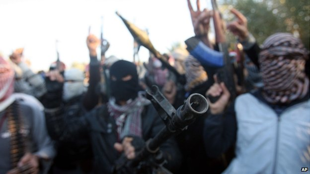 Gunmen gather in a street in Falluja as they chant slogans against Iraq's Shiite-led government