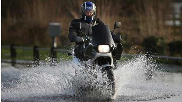 Motorcyclist drives through flooded road in Surrey