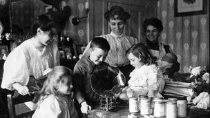 Women and children gathered around a gramophone at home during WW1.