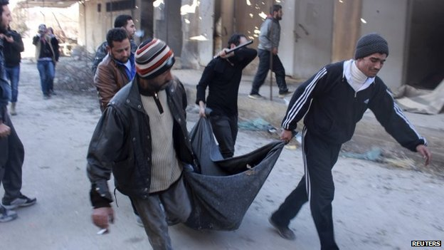 Men carry the body of a man apparently executed at an ISIS base in Aleppo (8 January 2014)