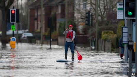 A man paddles a surfboard along a flooded road