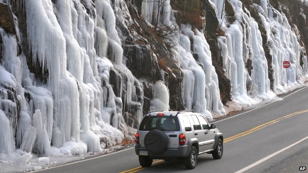 A motorist drives by the ice forming on a cliff along Route 61 in Palo Alto, Pennsylvania