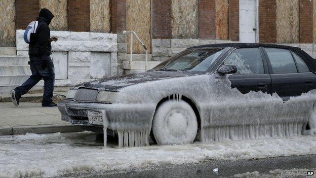 A man walks past a car partially covered in ice in Baltimore, Wednesday, Jan. 8, 2014, where temperatures continue to remain well below freezing