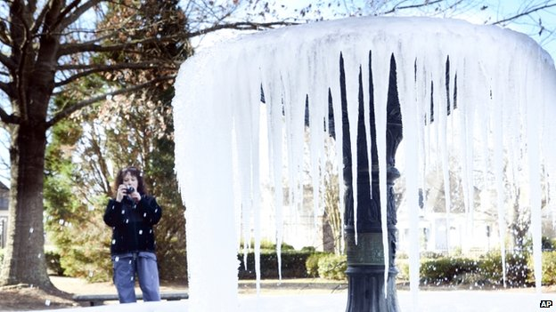 A woman takes photos of a frozen water fountain in Mississippi