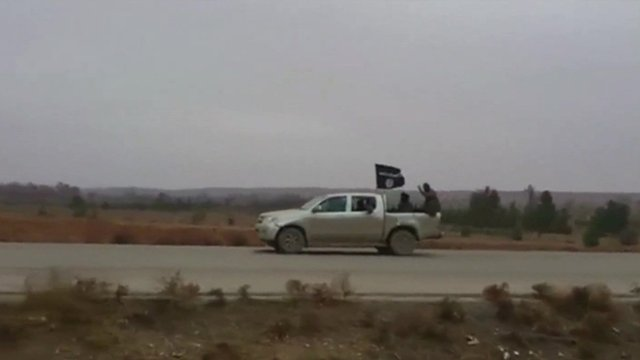 A still from video footage shows the black flag of the ISIS rebel group