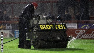 Ground staff attempt to clear water from the pitch during the FA Cup Second Round Replay match between Crawley Town and Bristol Rovers at Broadfield Stadium.