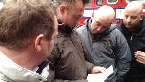 Firefighters gather around to read a card from a member of the public