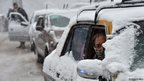 A taxi driver sits in traffic during a snowfall in Murree in Pakistan