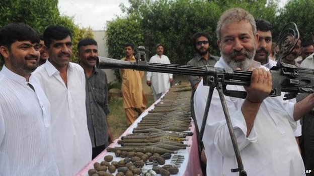 In this picture taken on May 11, 2012, Pakistan's senior police investigator Chaudhry Aslam holds a machine gun recovered from militants with other ammunition in Karachi, Pakistan.