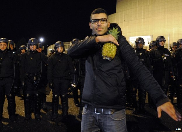 A man holds a pineapple and makes a quenelle salute outside the Zenith concert hall in Nantes, 9 January