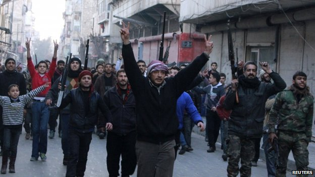 Civilians accompanied by Free Syrian Army fighters gesture as they march during a protest against fighters from the Islamic State in Iraq and the Levant (ISIS) in the Qadi Askar neighbourhood of Aleppo (7 January 2014)