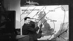 A black and white shot of a man with glasses, standing in front of a weather map. He has a pen in his hand and is drawing on the map.